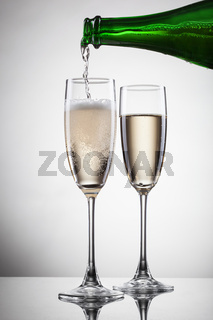 Champagne pouring into glass isolated on white