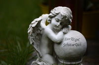 Marble angel with ball and quote: An Angel Shelter