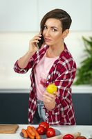 Talking on the phone showing a lemon young pretty woman with a bob hairstyle prepares food in the kitchen. Healthy food at home. Healthy food leaving - vegan concept. New house concept