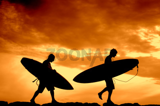 Vacation Silhouette Of Two Surfers Carrying Their Boards Home At Sunset