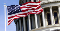 The flag of the united states of america flying in front of the capitol building blurred in the background