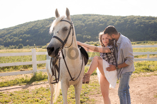 The young man helps his wife to get on a horse