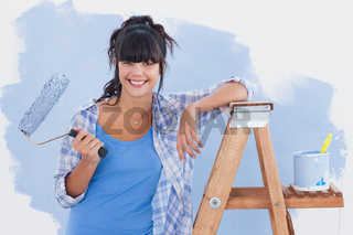 Woman holding paint roller leaning on ladder
