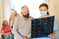 Senior Patient und Ärztin mit Mundschutz betrachten ein MRT