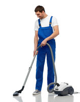 male worker cleaning floor with vacuum cleaner