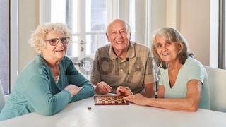 Gruppe Senioren als Rentner beim Dame spielen zu Hause