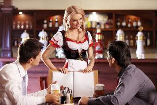 Attractive waitress shows visitors the menu bar