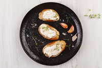 Baguette slices with garlic spread on black plate.