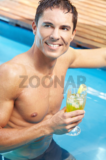 Mann mit Cocktail im Pool