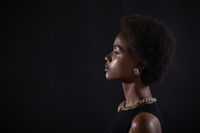 Close up portrait of african american woman with afro hairstyle on black studio background