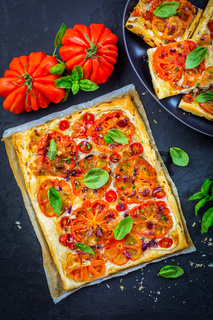 Vegetarian tomato tart or puffed pizza with herbs on black background