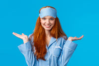 Who knows, dont care. Carefree and unbothered happy smiling redhead female in nightwear, sleep mask, shrugging indecisive and clueless with hands raised sideways, standing blue background