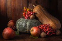 apples and pumpkin on a dark wooden background in a rustic style