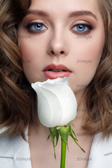 Woman in white jacket with blue eyes and white rose flower near face.