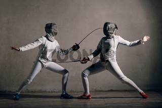 Fencer woman with fencing sword. Fencers duel concept