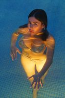 Beautiful woman in swimsuit swimming in water in pool at geothermal spa, balneotherapy resort