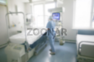 Blurred background of a hospital room with a silhouette of a doctor.