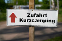 Signpost on a campsite in Germany with the inscription Access short camping (Zufahrt Kurzcamping)