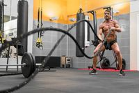 Muscular powerful man working out with rope in functional training fitness gym.