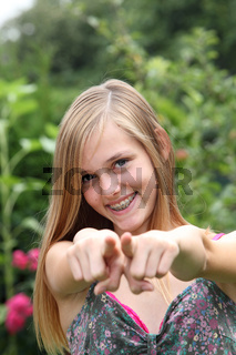 Young woman pointing her fingers at the camera