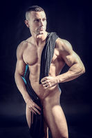 Totally naked muscular bodybuilder young man in studio