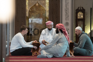 muslim people in mosque reading quran together