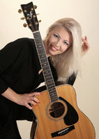 young fashion female model posing with guitar