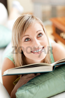 Attractive woman lying on a sofa reading a book