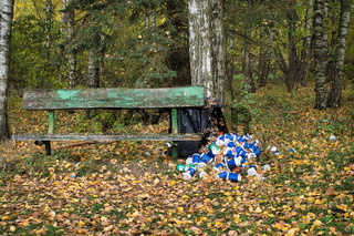 Pile of cans and containers alongside a rustic wooden bench