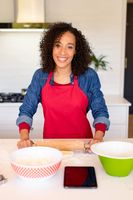 Portrait of happy african american woman wearing apron, baking in kitchen