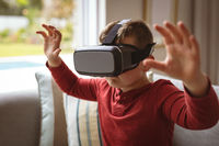 Caucasian boy wearing vr headset gesturing while sitting on the couch at home