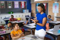 African american female teacher and caucasian boy talking in hand sign language at elementary school