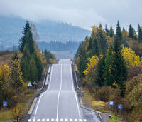 Hazy and overcast Carpathian Mountains and highway on mountain pass, Ukraine.