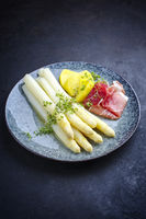 Traditional steamed white asparagus with cured ham and boiled potatoes garnished with butter sauce served as close-up on a Nordic design plate with copy space