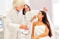 Hautarzt und Kollegin bei Beratung einer jungen Frau