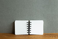Blank notebook on wooden desk. gray wall background