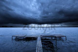 Old pier over dramatic story clouds. Zalew Zegrzynski