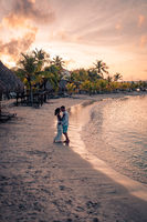 Couple on the beach of Curacao during sunset, men and woman watching sunset on the tropical beach of Curacao