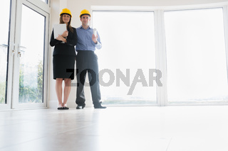 Man and woman holding clipboard and blueprint