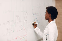 African American woman math teacher stands at blackboard with marker