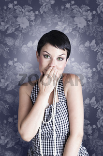 Portrait of surprised attractive brunette covering her mouth by the hands, over vintage background