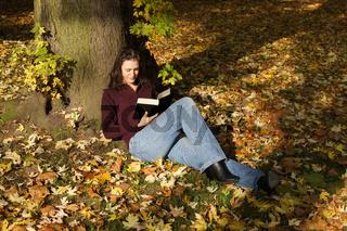 junge Frau liest Buch in Herbstszene
