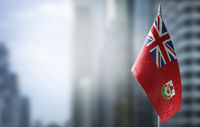 A small flag of Bermuda on the background of a blurred background