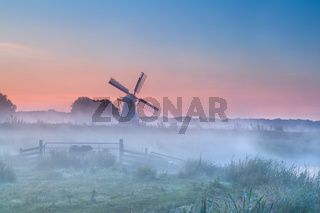 Dutch windmill in dense morning fog