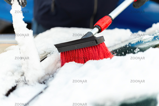 Person with broom brushing snow from windshield in close-up