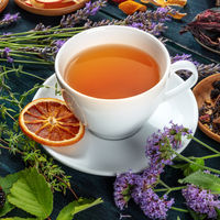Tea with herbs, flowers and fruit, on a dark rustic wooden background