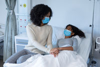 Mixed race mother comforting ill daughter in hospital bed, holding hands, both wearing face masks