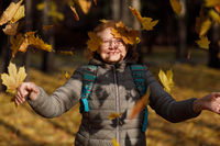 Adult mature fall woman throw up autumn leaves outside in colorful fall forest.