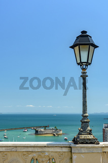 Old lamppost on a wall overlooking the sea and historic fortification in Salvador city