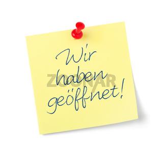 Yellow paper note with text  We are open in german - Wir haben geöffnet